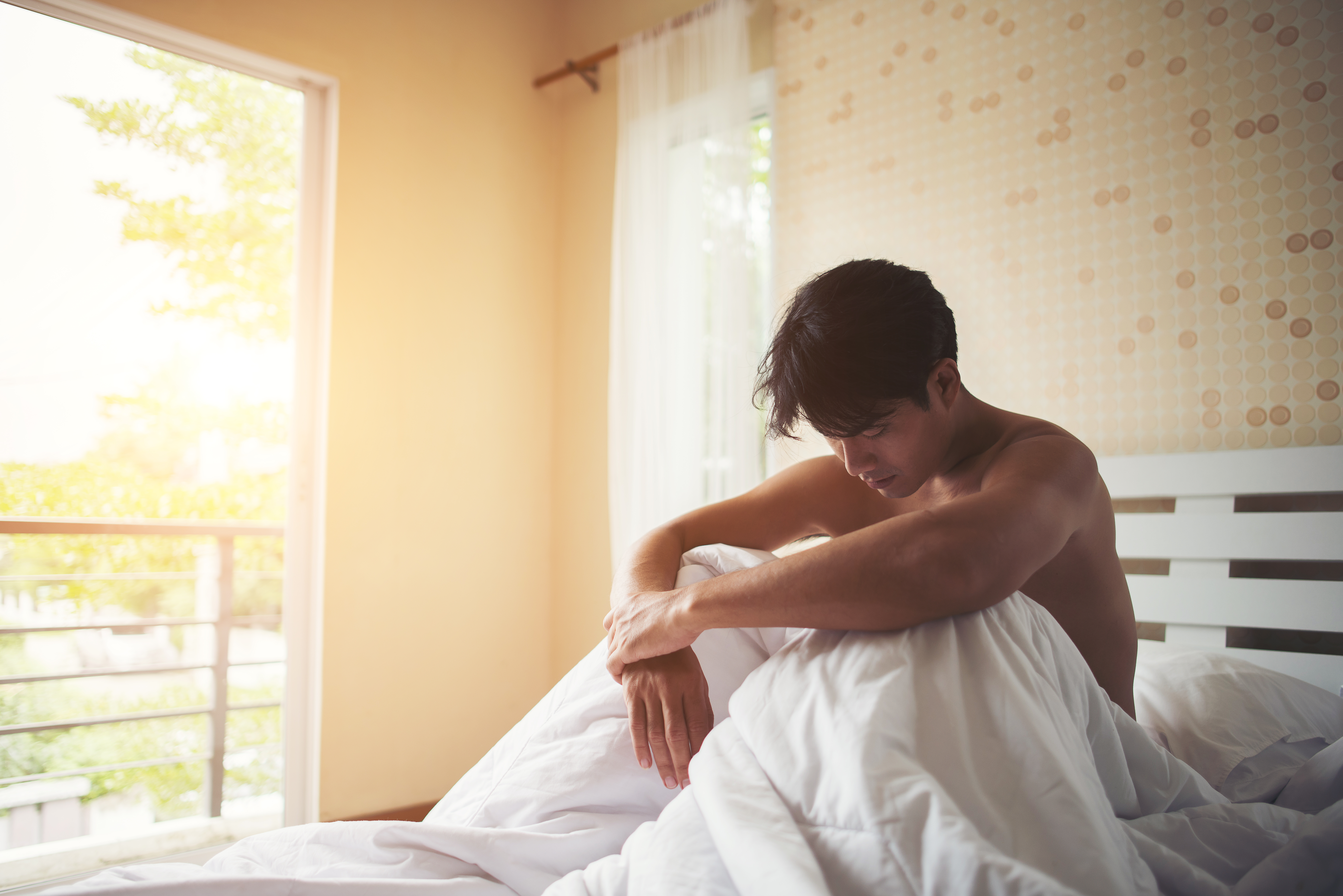 Worried man sitting on bed in the morning, serious thinking some